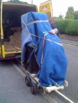 Baby grand piano on a moving shoe being loaded onto the van by SW Piano Movers.