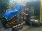 A 6ft grand piano being unloaded from the van by SW Piano Movers.